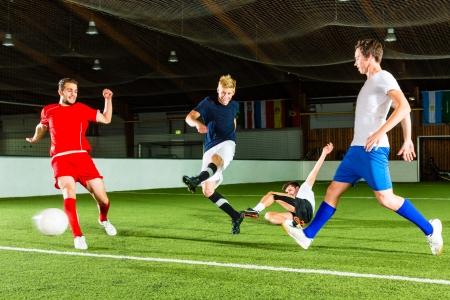 M�nner-Team Fu�ball spielen oder Fu�ball Indoor und versuchen, ein Tor zu erzielen Lizenzfreie Bilder