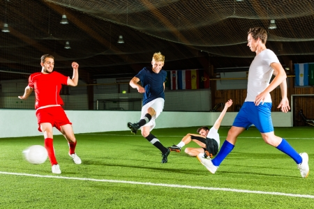 Men team playing football or soccer indoor and trying to score a goal photo
