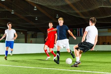 jugando al futbol: Hombres equipo que juega al f�tbol o f�tbol sala y tratar de marcar un gol