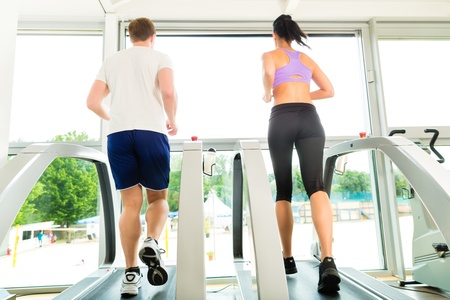 fitness center: Running on treadmill in gym or fitness club - man and woman exercising to gain more fitness