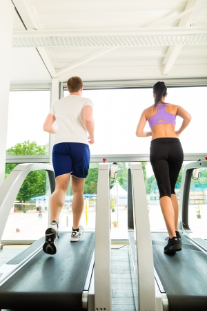fitness club: Running on treadmill in gym or fitness club - man and woman exercising to gain more fitness
