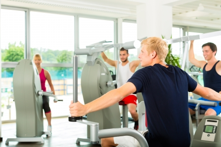 men exercising: Group of men train on machine in a fitness club or gym