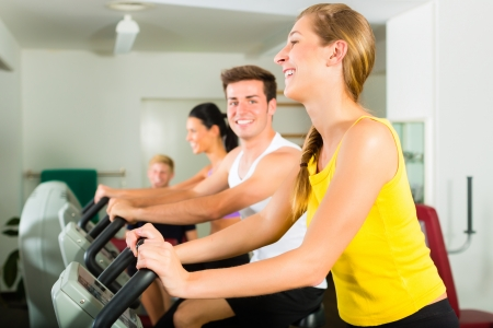Group of men and women train on machine in a fitness club or gym Stock Photo - 17049500
