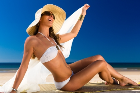 Attractive woman in a white bikini and sunhat sitting in the sun with a beach towel on the beach against a blue sky  photo