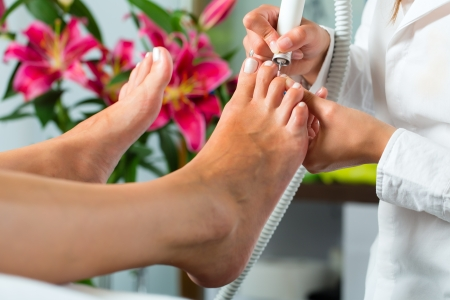 Woman receiving pedicure in a Day Spa, feet nails get cut and filed Stock Photo - 17058423