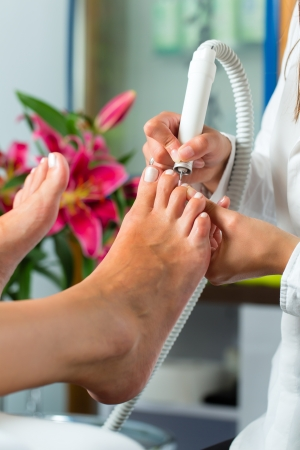 Woman receiving pedicure in a Day Spa, feet nails get polish Stock Photo - 17058416