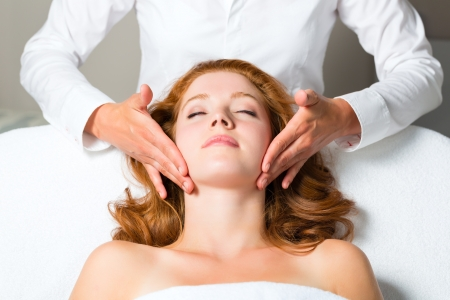 Wellness - woman getting massage in Spa, it is a massage for the head or face photo