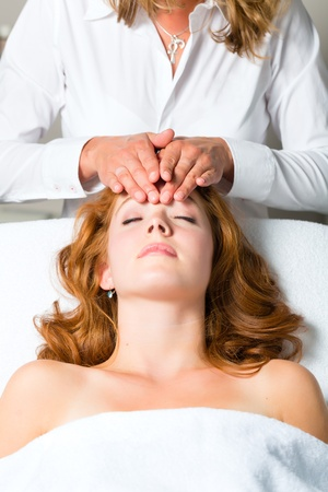 therapist: Wellness - woman getting massage in Spa, it is a massage for the head or face