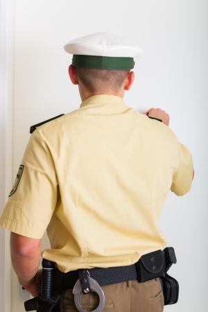 tocar la puerta: Oficial de policía llamando a la puerta principal de la casa Foto de archivo