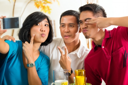 group picture: Asian friends, two men and a woman, having fun taking pictures with mobile phone