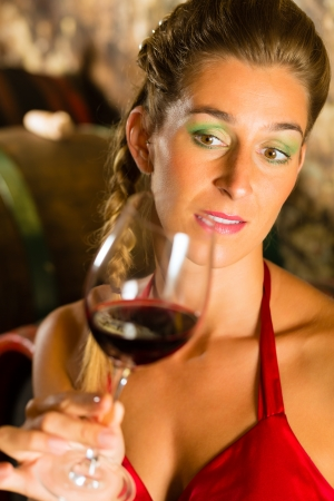 Woman keeping glass of wine in hand and looking skeptically in wine cellar Stock Photo - 17058430