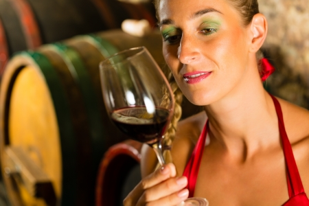 judged: Woman keeping wine glass in hand in the background wine barrel in wine cellar