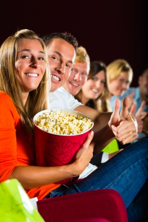 movie popcorn: People see a movie in the cinema and have fun they smile at the camera