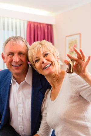 Senior couple sitting on the bed in the hotel room and the woman has a key in her hand Stock Photo - 17058419