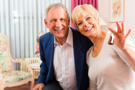 Senior couple sitting on the bed in the hotel room and the woman has a key in her hand Stock Photo - 17058451
