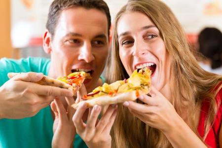 pareja comiendo: El hombre y la mujer que come una pizza y disfrutar de la noche Foto de archivo
