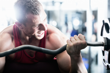 buildup: Strong man - bodybuilder with dumbbells in a gym, exercising with a barbell Stock Photo