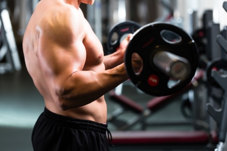 hand movements: Strong man - bodybuilder with dumbbells in a gym, exercising with a barbell Stock Photo