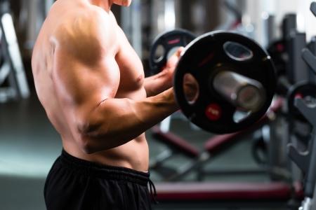 levantando pesas: Strong man - culturista con pesas en un gimnasio, hacer ejercicio con una mancuerna Foto de archivo