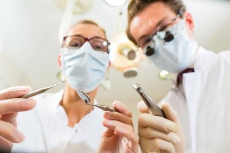 Zahnarzt und Assistent an einer Behandlung, aus der Perspektive eines Patienten