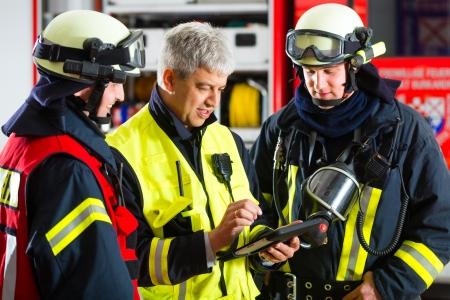 bombero de rojo: Bomberos - Squad líder da instrucciones, utilizó el Tablet PC para planificar el despliegue Foto de archivo