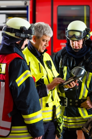 brigade: Fire brigade - Squad leader gives instructions, he used the Tablet Computer to plan the deployment Stock Photo