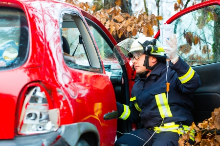 Accident - Fire brigade rescues accident Victim of a car, firefighter holds a drip for Infusion Stock Photo - 17058412