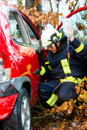 wrack: Accident - Fire brigade rescues accident Victim of a car, firefighter holds a drip for Infusion