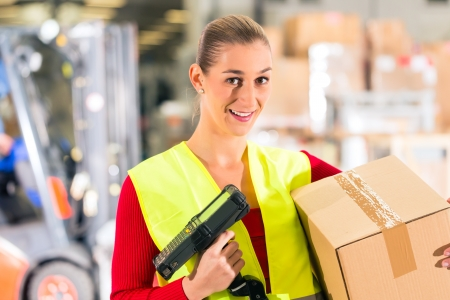 shipper: Female worker with protective vest and scanner, scans bar-code of package, standing at warehouse of freight forwarding company Stock Photo