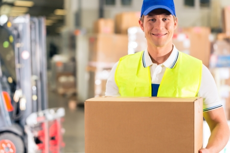warehouseman: Warehouseman with protective vest holds package, he standing at warehouse of freight forwarding company Stock Photo