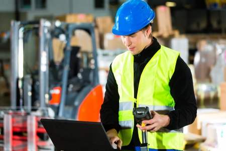 Warehouseman with protective vest, scanner and laptop in warehouse at freight forwarding company photo