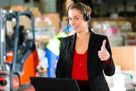 forwarding: Mujer Friendly, despachador o supervisor utilizando auriculares y un ordenador port�til en el almac�n de la empresa de transporte, sonriendo, un montacargas est� en segundo plano Foto de archivo
