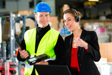 Teamwork - female supervisor and warehouseman or forklift driver with laptop and cell phone at warehouse of freight forwarding company - she pointing to the viewer photo