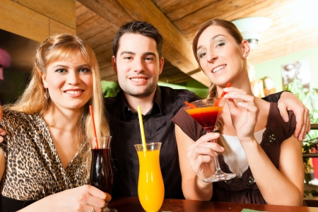 Young happy people drinking cocktails in bar or restaurant; presumably it is a little party photo