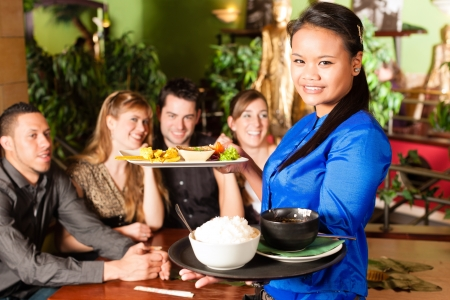 brings: Young people eating in a Thai restaurant; the waitress brings the dishes, rice and others