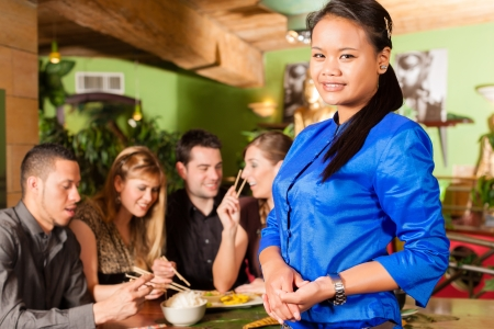 Young people eating in a Thai restaurant; the waitress brings the dishes, rice and others photo