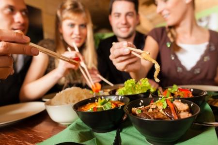 Junge Leute essen in einem Thai-Restaurant, sie essen mit Stäbchen