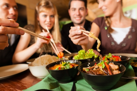 woman eat: Young people eating in a Thai restaurant; they eating with chopsticks