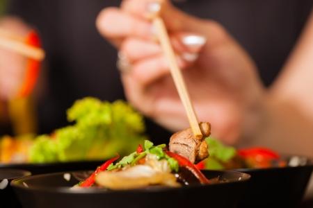 Jonge mensen eten in een Thais restaurant, ze eten met stokjes, close-up op handen en voedsel Stockfoto