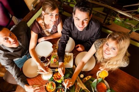Jonge mensen eten in een Thais restaurant, ze eten met stokjes Stockfoto