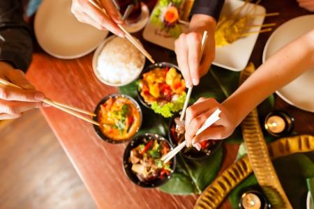 Junge Leute essen in einem Thai-Restaurant, Essen sie mit Stäbchen, close-up auf Händen und Lebensmittel Standard-Bild - 17109050