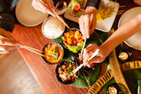 chopstick: Young people eating in a Thai restaurant, they eating with chopsticks, close-up on hands and food