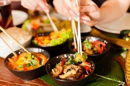 comida: Los jóvenes que comen en un restaurante tailandés, que comer con palillos, primer plano en las manos y los alimentos