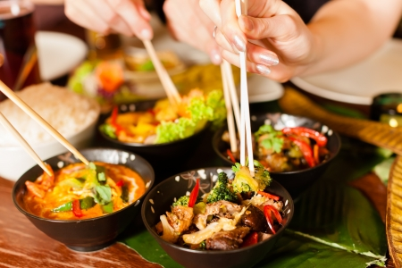 chinese food: Young people eating in a Thai restaurant, they eating with chopsticks, close-up on hands and food