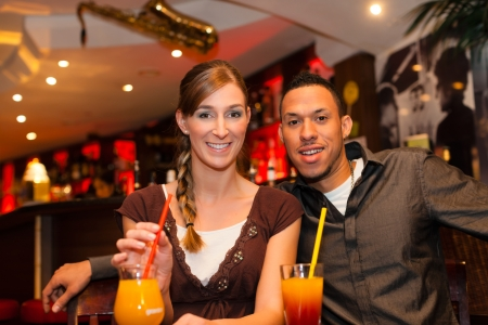 Young happy couple drinking cocktails in bar or restaurant, presumably it is a first date photo