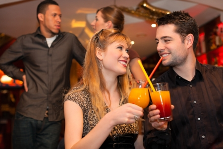 Young happy couple drinking cocktails in bar or restaurant, friends are standing in the background photo