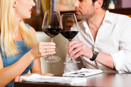 first date: Attractive young couple drinking red wine in restaurant or bar, it might be the first date