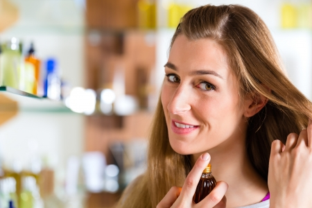 Young woman buying perfume in a shop or store, testing the fragrance on the neck or hair photo