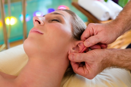 Woman enjoying head massage or lymphatic drainage in a spa  photo