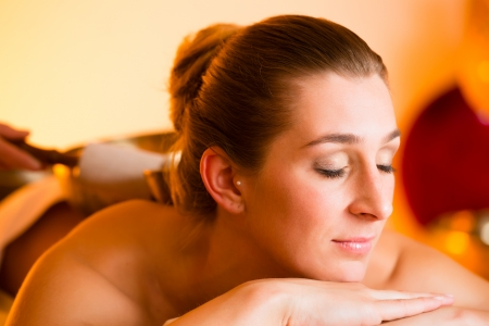 Woman in wellness and spa setting having a singing bowl massage therapy photo